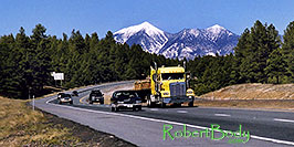 /images/133/2003-08-flagstaff-peaks3-pano.jpg - #01291: cars and yellow Semi Truck leaving Flagstaff and San Francisco Peaks behind … August 2003 -- Humphreys Peak, Flagstaff, Arizona