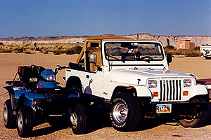 white Jeep Wrangler and ATV in the morning at Lone Rock