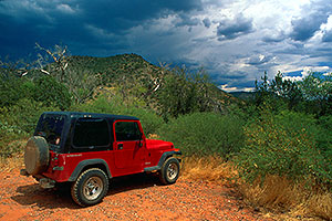 red Jeep Wrangler during monsoon season at Wet Beaver Creek by Sedona