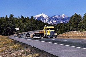 cars and yellow Semi Truck leaving Flagstaff and San Francisco Peaks behind
