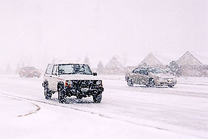 white Jeep Cherokee and cars in November snow, along Yosemite Road in Lone Tree