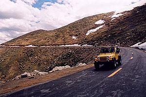 yellow Jeep Wrangler driving down from Mt Evans