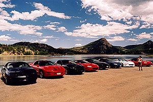 Ola photographing black, red and white Pontiac TransAm cars at Estes Lake