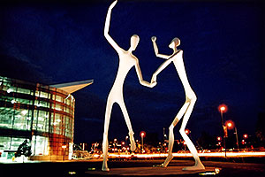 Denver Figures at night (by Performing Arts Center)
