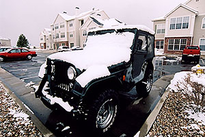green Jeep Wrangler with late season snow (even April brings snowstorms in Denver suburbs)