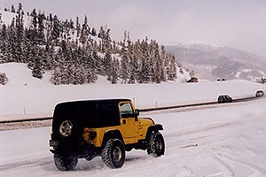 yellow Jeep Wrangler at overview of Dillon Lake