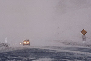 Jeep Wranger in snowstorm reaching top of Loveland Pass from Keystone side