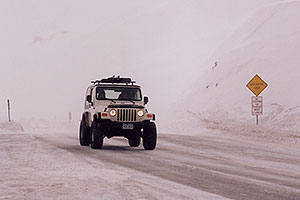 white Jeep Wranger in snowstorm at top of Loveland Pass