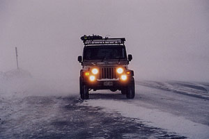grey Jeep Wrangler in snowstorm at top of Loveland Pass