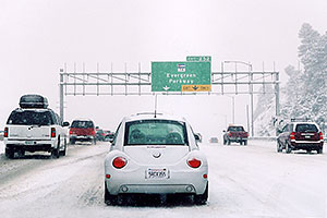 white VW Beetle Bug from California in a land of SUVs, during blizzard on Highway I-70 west of Golden