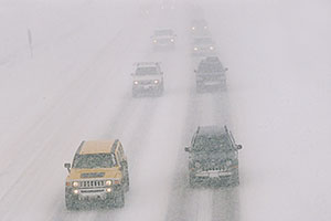 yellow Hummer H3 and grey Jeep Liberty, during blizzard on Highway I-70 west of Golden, heading to Denver