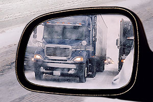 blue Semi truck in my side mirror, during blizzard on Highway I-70 west of Golden