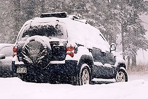 grey Jeep Liberty during a March snowstorm near Golden
