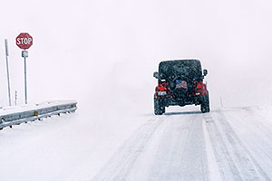 Red Jeep Wrangler entering the blizzard