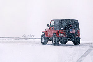 Red Jeep Wrangler turning off Highway I-70