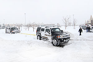 Snowplow rescuing two Police Hummers