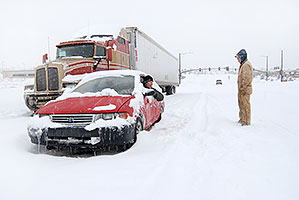 red Toyota and semi truck waiting for I-25 to open during a December snowstorm