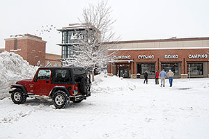 red Jeep Wrangler and people walking to REI #61 in Englewood, Colorado