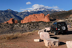Land Rover Discovery overlooking Garden of the Gods with Pikes Peak in the clouds