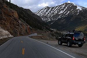 Car driving up the Twin Lakes side of Independence Pass Road, with Mount Champion at 13,646 ft
