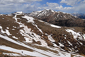 Skier walking across a snowfield on Mt Elbert … view of Mt Massive at 14,421 ft
