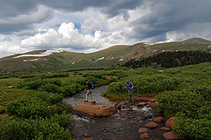 Hikers crossing Scott Gomer Creek along the trail of Mt Bierstadt