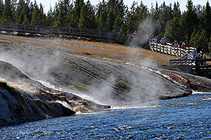 People returning from Excelsior Geyser Crater, and spring water flowing into Firehole River