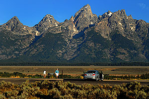 Photographer taking pictures in the morning of Grand Teton (center)