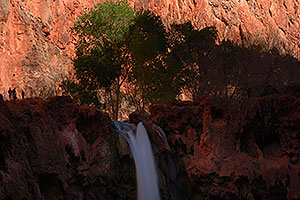 People next to Mooney Falls in the afternoon - 210 ft drop (64 meters)