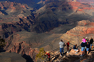 Girl in pink on dad`s shoulders and people enjoying views from Yavapai Point in Grand Canyon