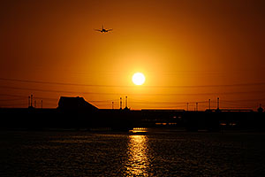 Plane flying into the sun at Tempe Town Lake