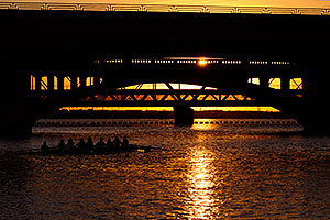 8 person sculling boat under Mill Road bridge at sunset at Tempe Town Lake