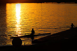 2 single scullers landing at the docks of North Bank Boat Ramp at Tempe Town Lake at sunset