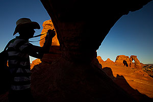 Photographer silhouette and view of Delicate Arch in Arches National Park