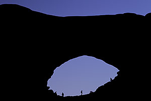 Silhouettes of people in North Window in Arches National Park