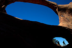 Hikers at Double O Arch in Arches National Park