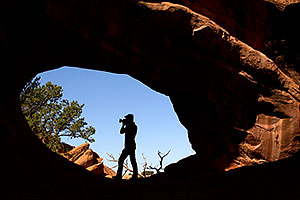 Photographer silhouette at Double O Arch in Arches National Park