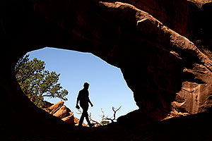 Hiker silhouette at Double O Arch in Arches National Park