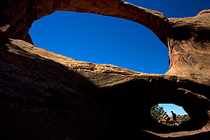 People at Double O Arch in Arches National Park