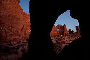 View of Double Arch through Cove Arch in Cove of Caves in Arches National Park