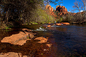People jumping across rocks by Cathedral Rock and Oak Creek in Sedona