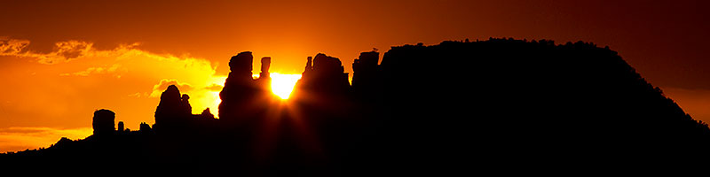 Sun setting behind rock formations in Sedona