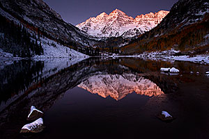 Snowy reflection of Maroon Bells with an icy cover along the shore