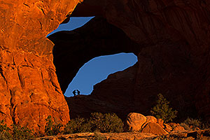 People silhouettes at Double Arch in Arches National Park
