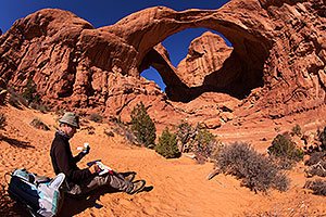 Artist drawing at Double Arch in Arches National Park